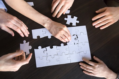 Corporate team people collaborating connecting puzzle on desk working together on strategy finding business solutions for successful teamwork engaged in teambuilding, unity concept, top close up view