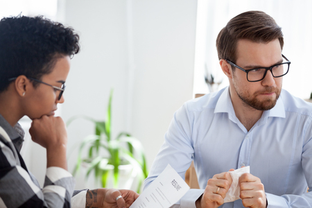 Serious african woman holding looking at resume paper, stressed diffident man candidate fumbling with a handkerchief in hands nervous during interview. Human resources recruitment and hiring concept Stock Photo