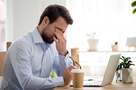 El hombre de negocios sentado en el escritorio en la oficina en el lugar de trabajo se quitó las gafas y se frotó los ojos. Fatiga y estrés en el trabajo, mala visión e influencia de la computadora en la salud humana, concepto de exceso de trabajo Foto de archivo