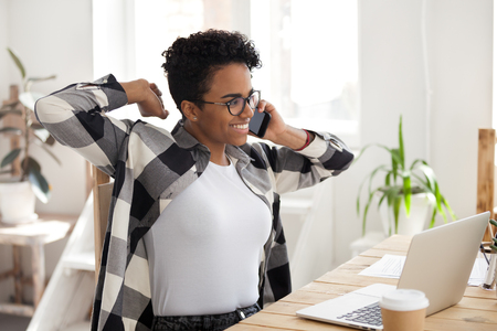 Satisfied black businesswoman worker in eyeglasses hold mobile phone talk sitting at the desk in front laptop in office. Millennial girl finish work relaxing after working hard day no stress concept