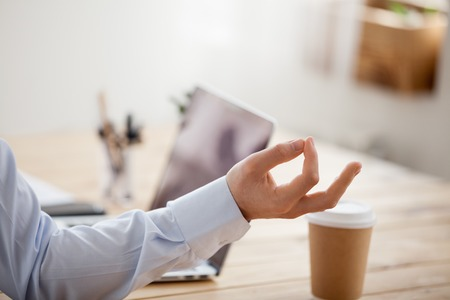 Male sitting in workplace in front of laptop and taking break for meditation, focus on hand close up. Thinking, focusing, stress relief, healthy good habits, mental health, mindful lifestyle concepts