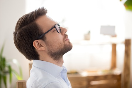 Close up of attractive millennial businessman relaxing after work breathing fresh air sitting in office room with closed eyes. Person dreaming thinking about work, career and prosperous future concept Banco de Imagens