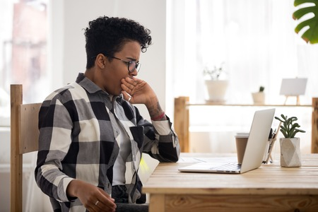 Exhausted African businesswoman in eyeglasses sitting at the desk in office room. Worker or student woman yawning cover mouth with hand, feels tired after hard working day. Fatigue overworking concept Stock Photo