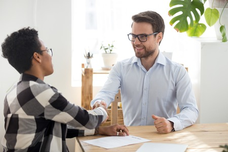 Black american boss advisor woman sitting with candidate businessman in office. Confident man african woman businesspeople shaking hands. Deal, agreement or successfully passed interview HR concept