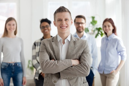 Smiling millennial confident businessman stands with arms crossed looking at camera with happy cheerful business partners team on background. Successful teamwork, company owner and leadership concept Stock Photo