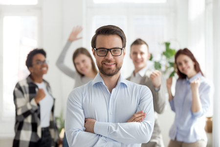Smiling millennial confident businessman standing with arms crossed looking at camera with happy cheerful business partners team at background. Successful teamwork, business owner company boss concept Stock Photo