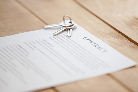 Close up of keys lying on a contract document paper on a wooden table. New dwelling or home successful real estate deal, buying selling, renting and tenancy, mortgage and loan concept, focus on keys