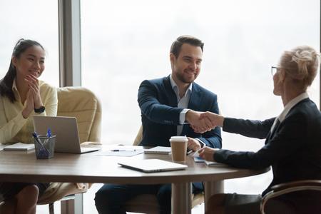 Geschäftsfrau Händeschütteln des männlichen Kollegen, der ihn mit Beförderung begrüßt, weiblicher Chef-Handshake-Partner, der mit Abschlussvertrag oder Vertragsunterzeichnung gratuliert und sich für das Treffen bedankt. Kooperationskonzept Standard-Bild