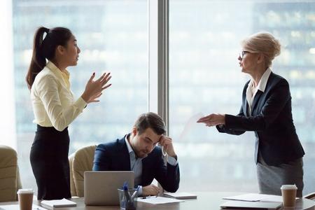 La empresaria de mediana edad enojada tiene una disputa con un joven empleado asiático que culpa por error en los documentos, las parejas femeninas entran en conflicto discutiendo en una reunión de negocios, acusando en incumplimiento del contrato Foto de archivo