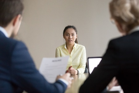 Back view of recruiters interview young Asian job candidate asking questions, reading her resume, hr managers hiring employee, considering cv experience, worried intern talk at recruitment process Stock Photo - 109537859