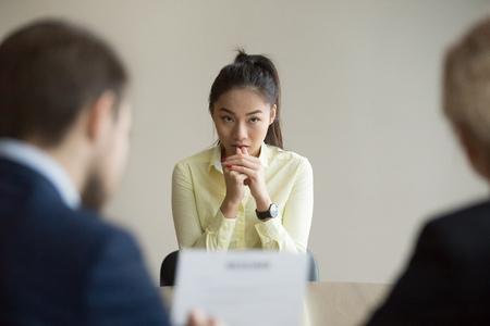 Nerveuze jonge Aziatische sollicitant wacht op vraag van recruiters tijdens een sollicitatiegesprek op kantoor, bezorgde stagiair of stagiair voelt zich gestrest bij het solliciteren naar een open positie, ontmoeting met hr-managers. Inhuren concept Stockfoto