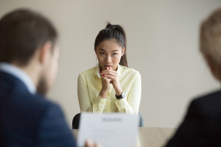 Nervous young Asian job applicant wait for recruiters question during interview in office, worried intern or trainee feel stressed applying for open position, meeting with hr managers. Hiring concept Archivio Fotografico - 109537860