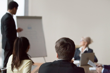 Male employee make presentation on flipchart for office colleagues at business meeting, man presenting project on whiteboard before partners during briefing in boardroom, mentor coach workers