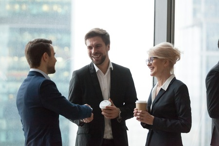 Smiling office workers talk having casual conversation, get acquainted during meeting, excited colleagues handshaking introducing at coffee break at briefing, happy workers greeting shaking hands Stockfoto