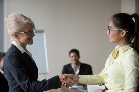 Female boss congratulate Asian employee handshaking and greeting her during meeting, happy businesswoman shake hand of woman worker complimenting with promotion or good work results. Reward concept Фото со стока - 109614794