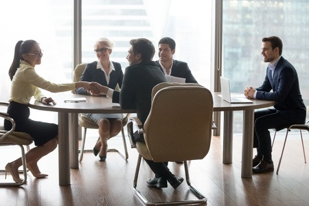 Colleagues handshake getting acquainted during company meeting in office, business partners shake hands introducing at negotiation, businessman congratulate female employee with promotion