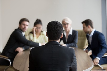 Back view of male African American job candidate recruit for position in office, HR team consider black applicant resume and candidature, recruiters asking questions at interview. Hiring process Stock Photo - 109614802