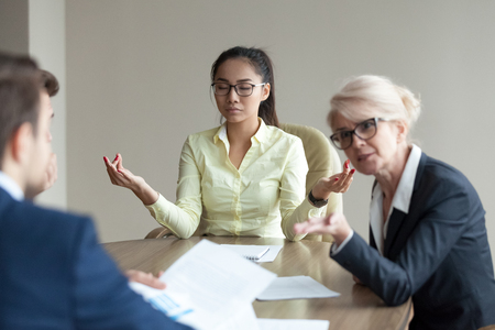 Calm Asian millennial worker meditate at office meeting not involved in disputes or arguments, peaceful young female employee practice yoga avoid conflict at negotiations. Stress free concept Banco de Imagens