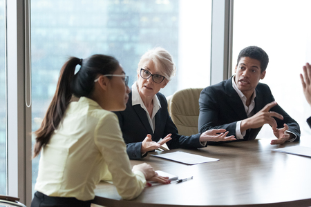 Diverse employees dispute with Asian female workers blaming her in failure or crisis, mad colleagues disagree with businesswoman accusing in company bankruptcy, coworkers have conflict at meeting