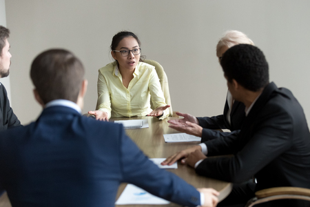 Young Asian employee speak explaining point of view to colleagues, excited millennial female worker talk emotionally to coworkers at business negotiations, woman argue at briefing reasoning decision Stock Photo