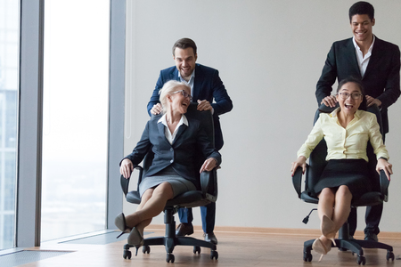 Excited multiethnic workers riding on chairs in office room, laughing diverse employees having fun engaged in teamwork activity at meeting, smiling colleagues enjoy playing funny game together
