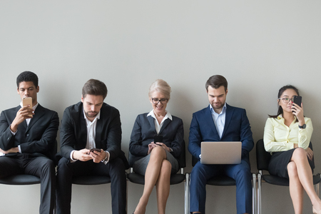 Happy multiethnic job applicants sit on chairs in corridor using gadgets before interview, diverse work candidates hold devices, browsing smartphone and laptop before talk. Hiring, employment concept Stock Photo - 109614849