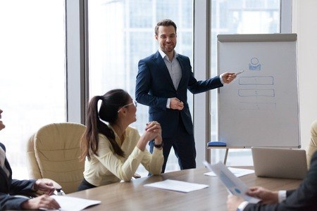 Smiling male employee present business project or idea on flipchart during casual negotiations, happy mentor or coach give whiteboard presentation to workers at friendly meeting in office Reklamní fotografie