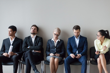 Diverse work candidates sitting in queue in office expecting their turn for interview, multiethnic job applicants waiting in corridor preparing for recruiting process. Employment, hiring, HR concept Stock Photo - 109614859