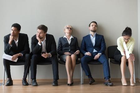 Multi-etnische sollicitanten in de rij moe van het lange wachten in de kantoorgang, diverse sollicitanten zitten op stoelen en voelen zich uitgeput in afwachting van hun beurt voor een sollicitatiegesprek. Werkgelegenheid, aanwerving, HR-concept Stockfoto