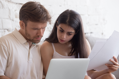 Stressed millennial young couple sitting on couch at home using notebook check unpaid bills, taxes, due debt, bank account balance. Bankruptcy, debt and shortage of money, financial problems concept 版權商用圖片 - 109614992
