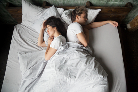 Young girl and guy, couple sleeping under blanket with their backs to each other in bed in bedroom at home, top view. Early morning, lazy Sunday weekend or day napping. People relaxing resting at home