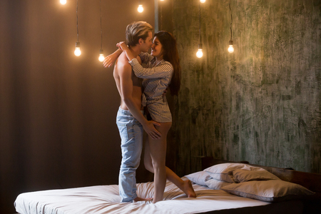 Happy shirtless man and woman in shirt embracing foreplay at romantic date standing on bed in bedroom at home. Newlywed couple celebrating moving at new flat or home. Romantic atmosphere, light bulbs