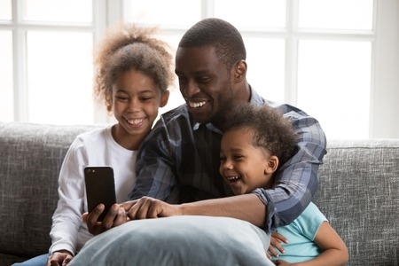Happy African family spending time have a fun together using mobile phone at home. Black father with little daughter and son make selfie photo picture watching video sitting on couch at sitting room