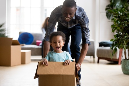 Black family in living room have a fun spend time at new home. African adorable playful laughing boy sitting at cardboard box, father rolling him playing together. New property and relocation concept