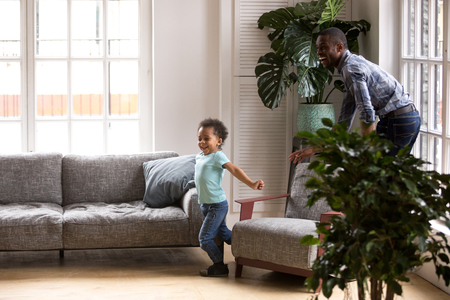 African American family dad and kid have a fun playing tags touch game spend free time on weekend at home. Cheerful father and little preschool toddler son catching each other running in living room 写真素材
