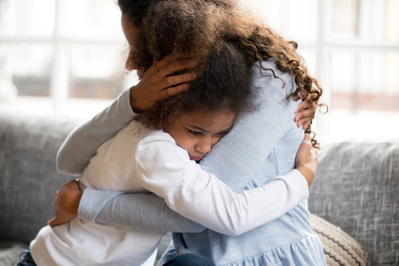 Black African mother embrace little preschool frustrated kid sitting on couch together at home. American loving mother supports disappointed daughter sympathizing, making peace after scolding concept Stockfoto