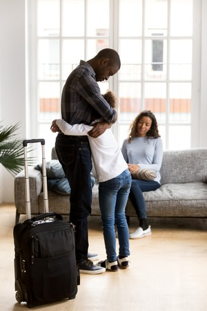 Married couple and little daughter in living room at home. Sad unhappy father hugs small daughter. Parents divorcing, break up, child stay with mommy dad leave with suitcase. Discord in family concept