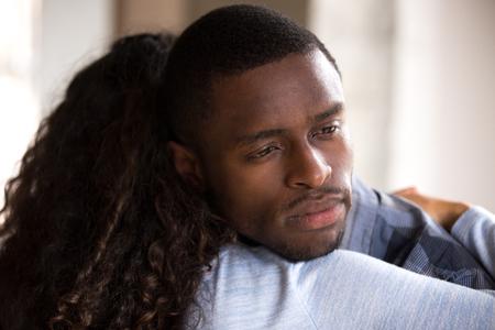Cerca de matrimonio americano abrazando. Esposa africana abrazando decepcionado marido frustrado triste, vista trasera de la mujer. La pareja infeliz tiene problemas en la relación, la amistad y el concepto de apoyo.
