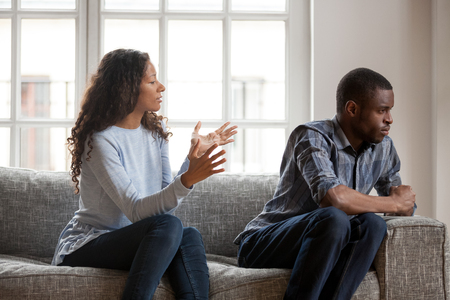 Black couple sitting on couch in living room at home and quarrelling. Unsatisfied wife negative emotionally talking with angry husband. Misunderstanding, break up and problems in relationship concept