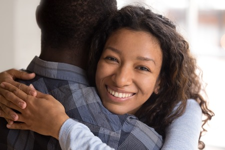 Portrait of black beautiful wife embracing husband. Close up african woman looking at camera, man rear view Attractive affectionate couple in love, romantic relationship just a married engaged concept Stock Photo