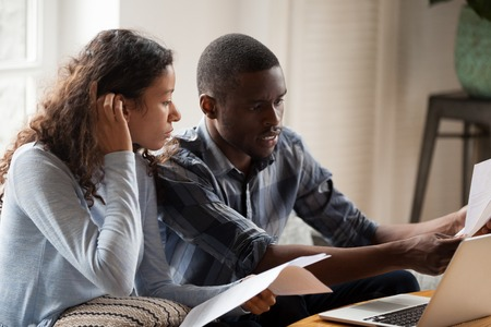 African Millennial stressed married couple sitting on sofa at home checking unpaid bills, taxes, due debt, bank account balance. Bankruptcy, debt and lack of money financial problems in family concept