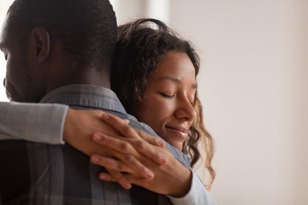 Sluit omhoog jonge zwarte Amerikaanse vrouw die echtgenoot omhelst. Portret van een vrouw met gesloten ogen, man achteraanzicht. Aantrekkelijk aanhankelijk verliefd koppel, romantische relatieondersteuning en dankbaarheid concept
