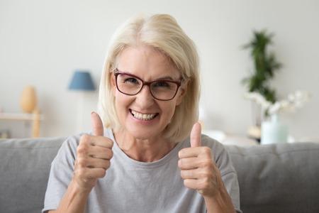 Opgewonden volwassen vrouw met een bril zit thuis op de bank en toont duimen omhoog tevreden met service, glimlachende oudere vrouw maakt een gebaar dat iets aanbeveelt, tevreden met keuze of beslissing Stockfoto
