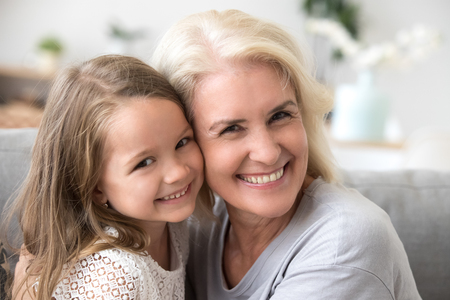 Portrait of happy grandmother and granddaughter spend time at home together, hugging and cuddling on couch, smiling granny embrace cute little grandchild looking at camera making family picture Imagens