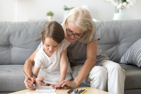 Grandmother and granddaughter paint picture with colorful pencils together, granny and grandchild have fun at home, drawing on paper, grandma spend time with little girl teaching depict things