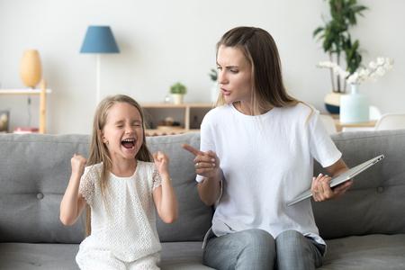 Hartnäckiges kleines Mädchen schreit laut, hört nicht auf strenge Mutter, ernsthafte junge Mutter schimpft Tochter für schlechtes Benehmen, arbeitende Mutter, die um Aufmerksamkeit bittet. Familienkonfliktkonzept