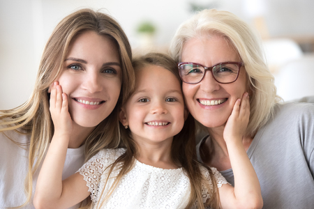 Portrait of three generations of women look at camera posing for family picture, cute little girl hug mom and granny enjoy time at home, smiling mother, daughter and grandmother spend weekend together Foto de archivo