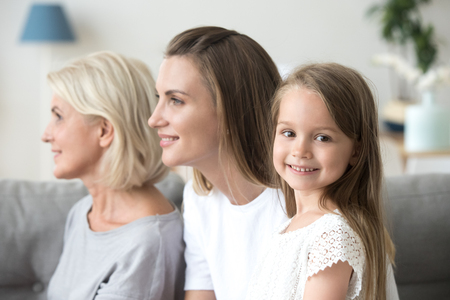 Portrait of cute little girl looking at camera smiling, mother and grandmother watch in distance imagining bright future for family, three generations of women in one picture, profile shot Stockfoto