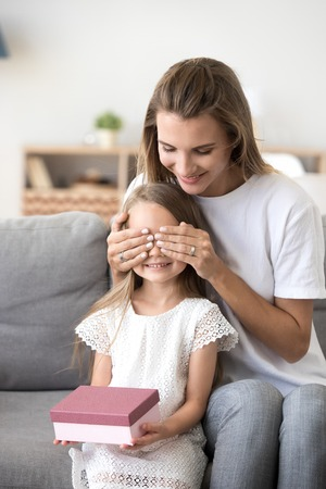 Happy young mom closing eyes making surprise for small cute daughter, mother congratulate little child presenting birthday box, girl receive gift from loving mommy, celebrating at home together 스톡 콘텐츠