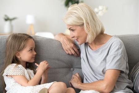 La niña linda y la abuela atenta se sientan en el sofá en casa y tienen una conversación informal, la abuela feliz habla con la nieta divirtiéndose, la abuela y el nieto pasan tiempo juntos comunicándose